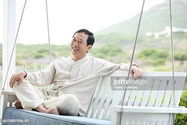 Mature man relaxing on porch swing