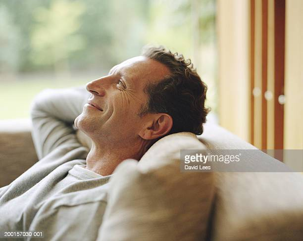 mature man relaxing on sofa, hands behind head, smiling, profile - zurücklehnen stock-fotos und bilder
