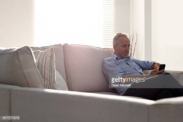 Mature man relaxing on sofa using a mobile phone
