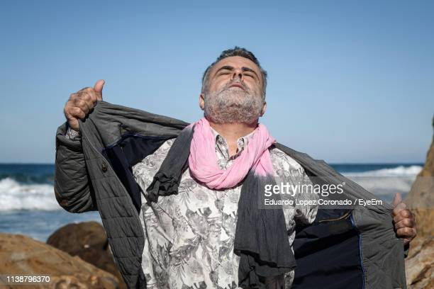Mature Man Removing Jacket While Standing At Beach