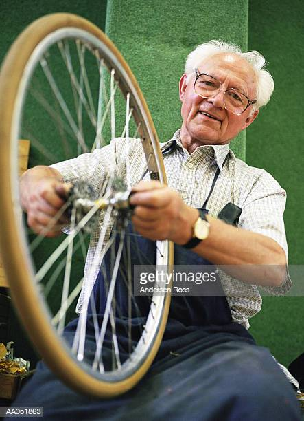 Mature man repairing bicycle tire, low angle view