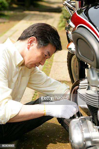 Mature man repairing motorbike, close-up