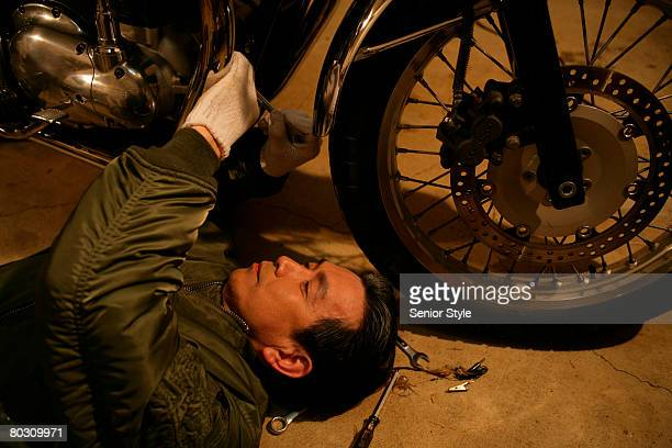 Mature man repairing motorcycle