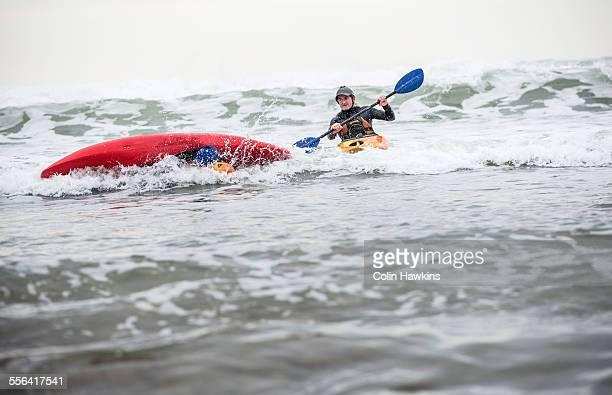 Mature man rescuing person fallen in sea in kayak
