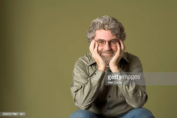 mature man resting chin on hands, smiling, portrait - tre quarti foto e immagini stock