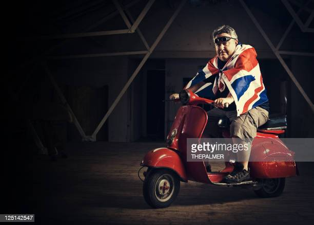 mature man ridding a vespa
