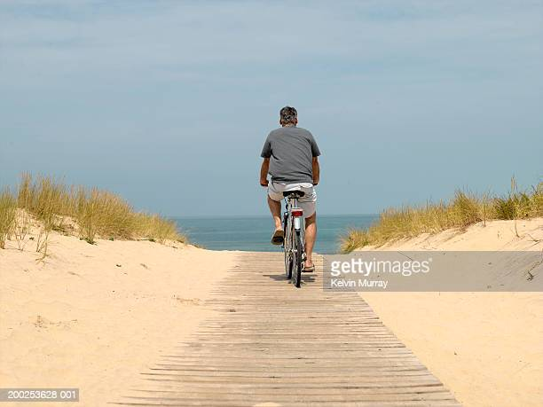 Mature man riding bicycle on path by beach, rear view