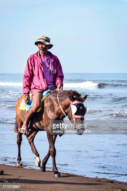 Mature Man Riding Horse On Shore At Beach Against Sky