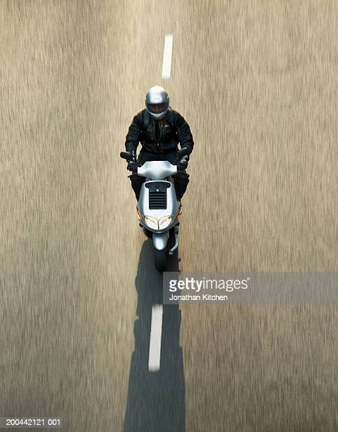 Mature man riding moped, (blurred motion) elevated view, sunset