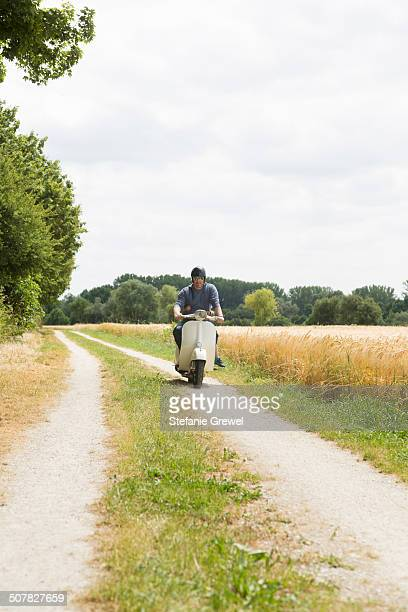 Mature man riding motor scooter along dirt track with daughter holding onto waist