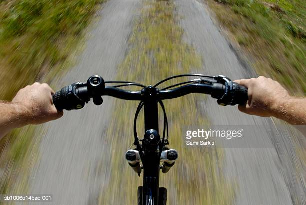 Mature man riding mountain bicycle (personal perspective)