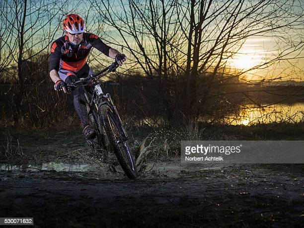 mature man riding mountain bike on dirt track, bavaria, germany - cross country cycling stock pictures, royalty-free photos & images