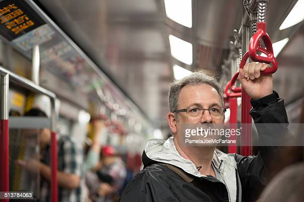 Mature Man Riding Train in Hong Kong