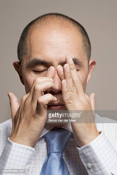 mature man rubbing pressure point between eyes, eyes closed, close-up - nariz humano imagens e fotografias de stock