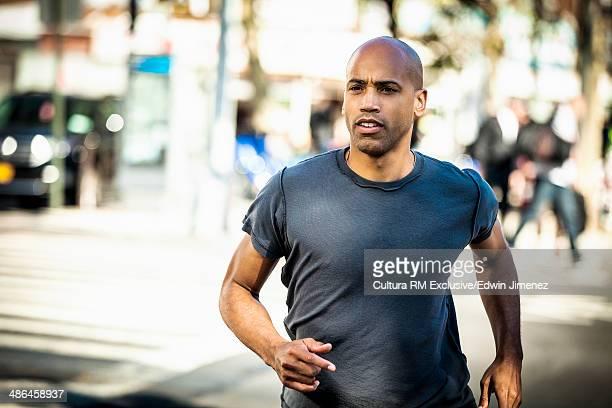 Mature man running along street, New York, USA