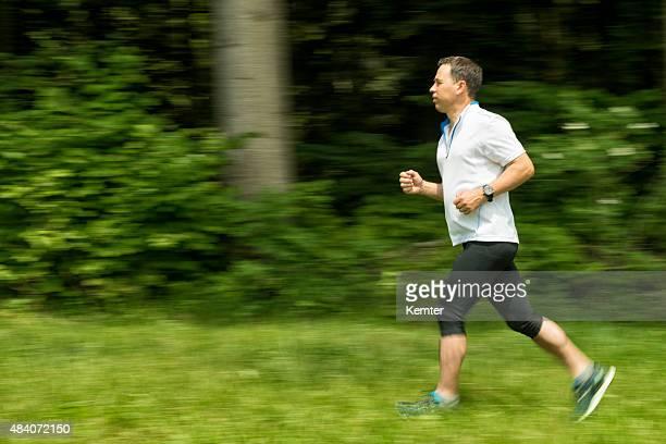 uomo maturo corsa nella natura - top bianco foto e immagini stock