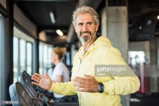 mature man running on a treadmill in the gym. - drug rehab stock pictures, royalty-free photos & images