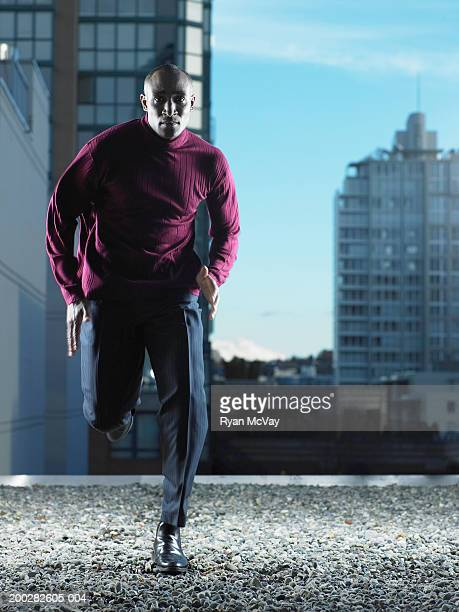 Mature man running on rooftop, portrait