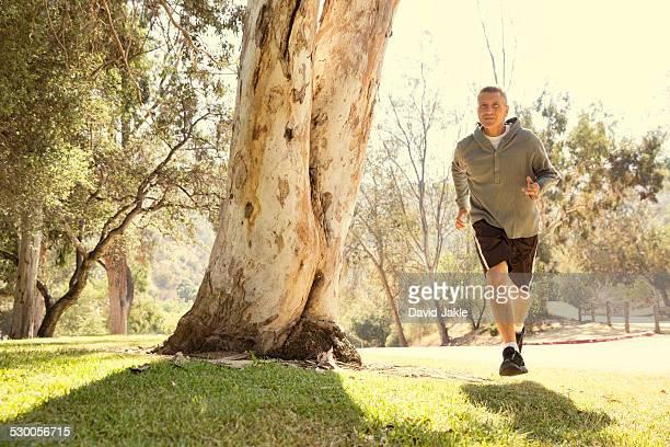 Mature man running through park