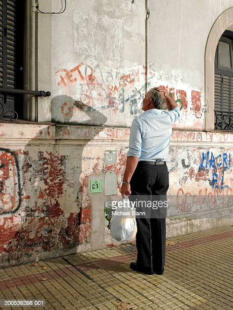 Mature man scratching his head at graffiti on wall