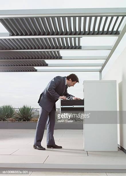 Mature man searching in filing cabinet