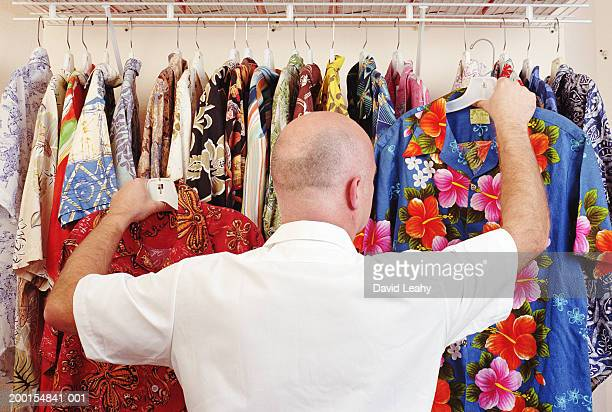 Mature man selecting Hawaiian shirts from rail, rear view