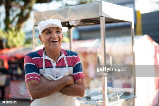 Mature Man selling churros at street portrait