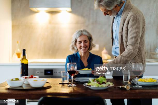 mature man serving dinner to his wife in kitchen at home - heterosexual couple stock pictures, royalty-free photos & images