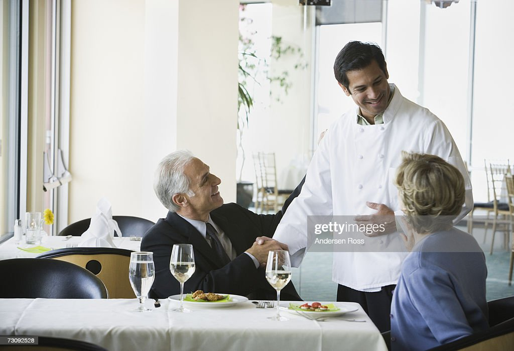Mature man shaking chef's hand, senior woman watching : Stock Photo