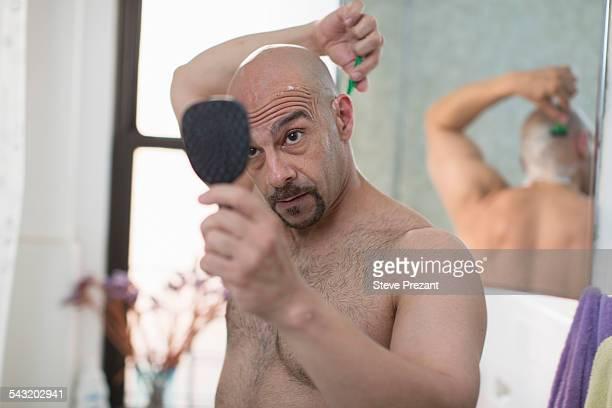 Mature man shaving his head in bathroom
