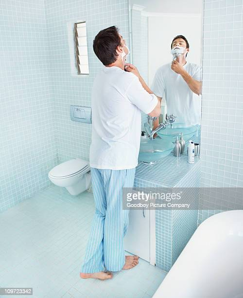 Mature man shaving in front of a bathroom mirror