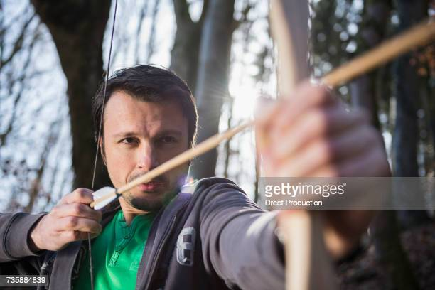 Mature man shooting with bow and arrow