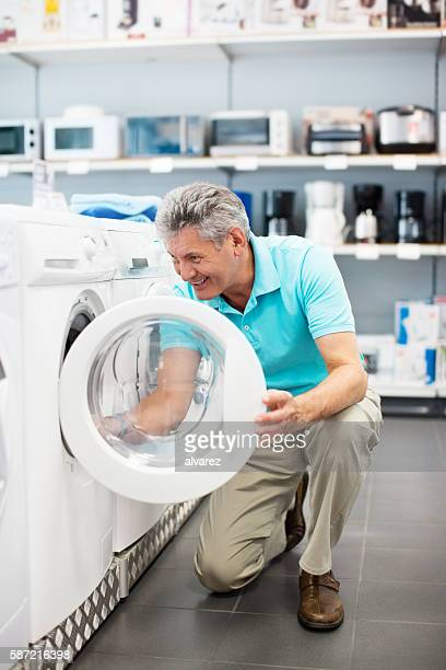 mature man shopping for a washing machine - electronics store stock photos and pictures