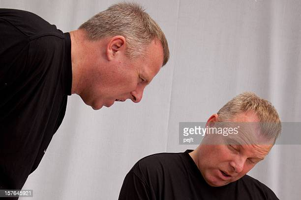 Mature man shouting and scolding at twin or identical male