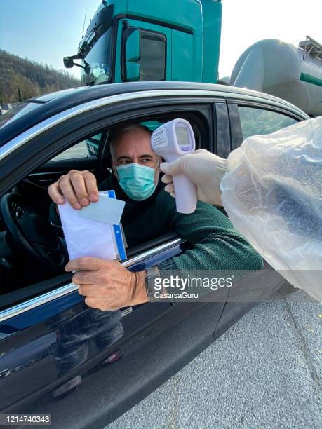 mature man showing id and work permission at border control with body temperature measurement during covid-19 crisis - infrared thermometer stock pictures, royalty-free photos & images