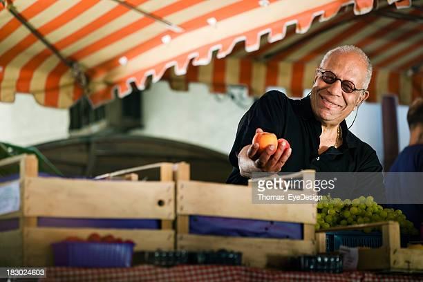 Reifer Mann mit Pfirsichen auf einem Markt