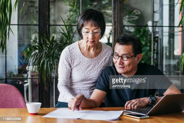 mature man showing woman document and pointing - retirement stock pictures, royalty-free photos & images