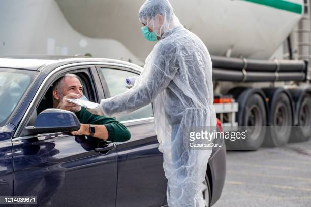 mature man showing working permission to cross the border - infrared thermometer stock pictures, royalty-free photos & images
