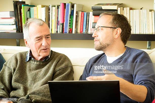 Mature man shows proof to senior man on laptop