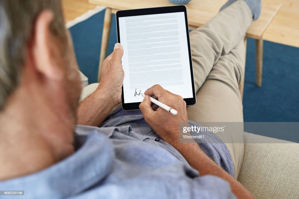 Mature man signing digital contract on tablet : Stock Photo
