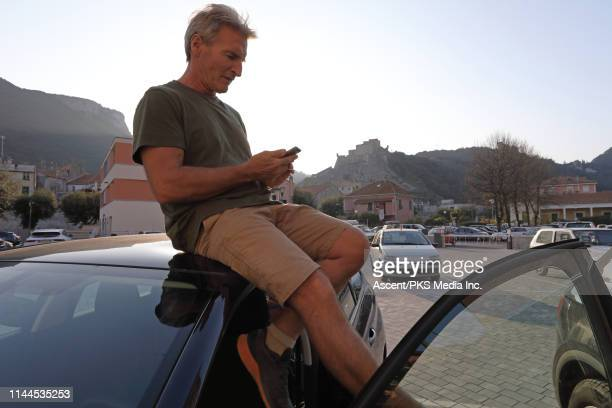 Mature man sits on car roof and texts on mobile phone