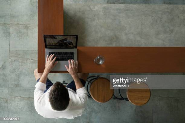 Mature man sittiing in kitchen, using laptop