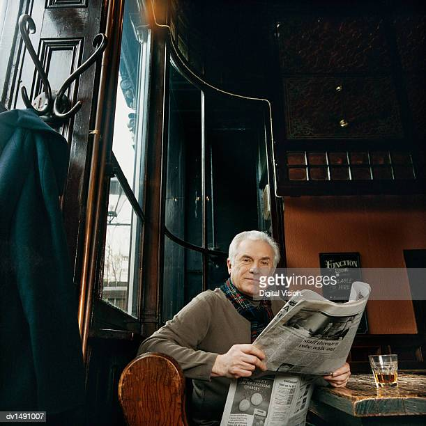 Mature Man Sitting at a Table in a Pub With a Newspaper