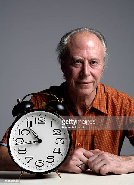 Mature man sitting at a table with an alarmclock