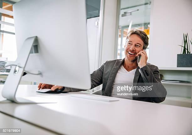 成熟した男性のシッティングエリアを備えたデスクで話しているスマートフォン