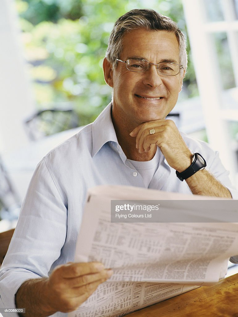 Mature Man Sitting at Home Holding a Newspaper : Stock Photo