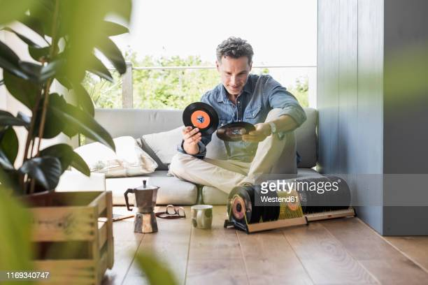 mature man sitting at home, looking at vintage sigle recors - collection photos et images de collection