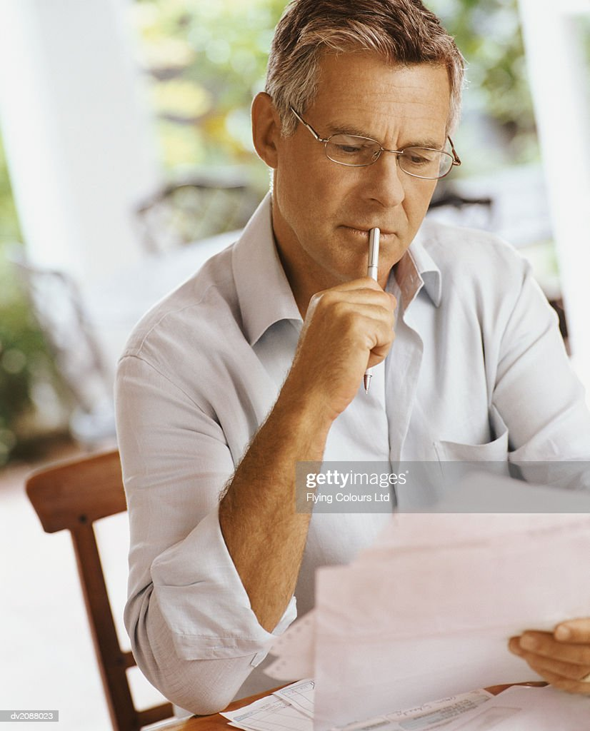 Mature Man Sitting at Home Reading a Letter : Stock Photo