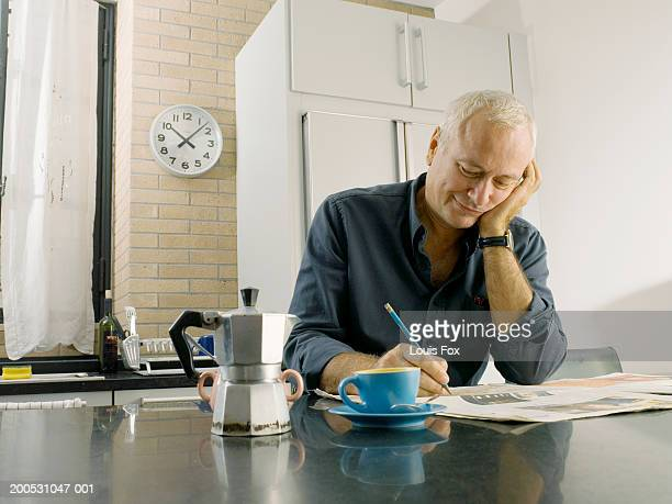Mature man sitting at kitchen table completing crossword, smiling