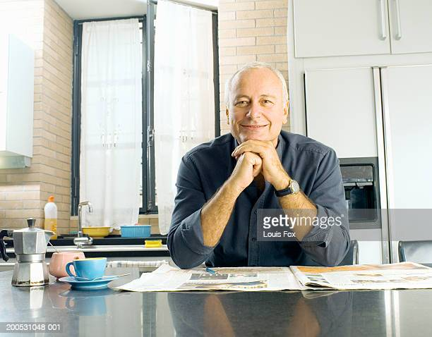 Mature man sitting at kitchen table with newspaper, smiling, portrait